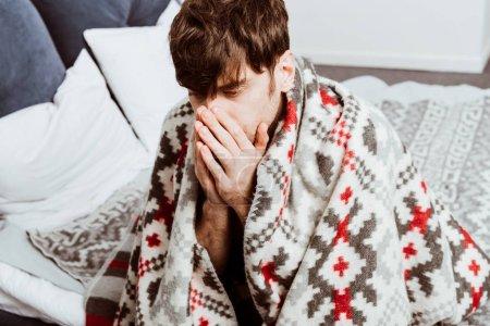 Photo pour Foyer sélectif du jeune homme malade enveloppé dans une couverture assise sur le lit à la maison - image libre de droit