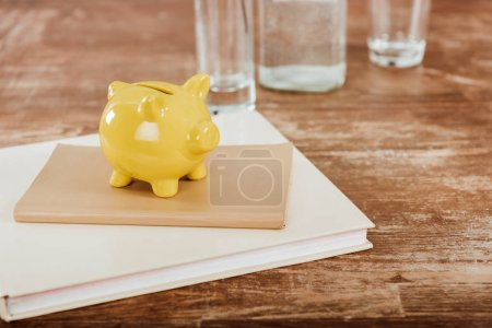 close up view of yellow piggy bank with textbook and book at wooden table