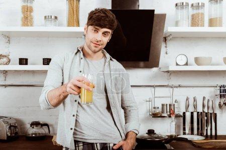 Foto de Enfoque selectivo de joven bebiendo jugo de naranja en el desayuno en cocina en casa - Imagen libre de derechos