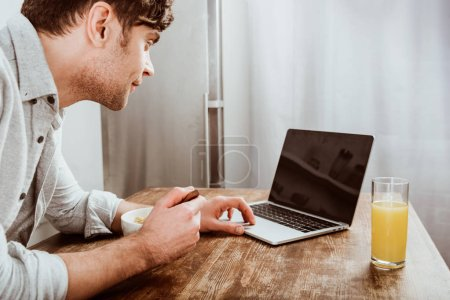 Photo pour Vue latérale du mâle pigiste manger des flocons de maïs et travaillant sur ordinateur portable avec écran blanc à table dans la cuisine - image libre de droit