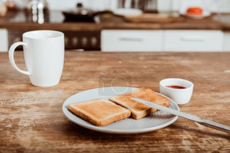 selective focus of toasts on plate, jam and coffee cup at table in kitchen