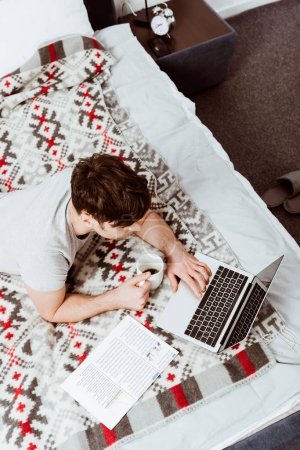 Photo for High angle view of male freelancer with coffee cup working on laptop in bed at home - Royalty Free Image