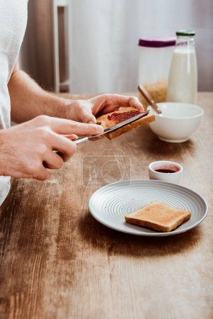 cropped image of man spreading toast by jam in kitchen at home