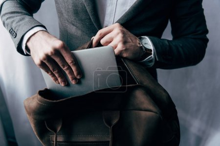 cropped image of businessman in jacket putting laptop in bag