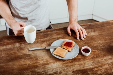 cropped image of man with coffee cup standing at table with toasts and jam in kitchen