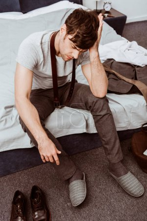 young businessman with belt over neck sitting on bed and having headache at home