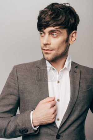 portrait of young handsome businessman looking away on grey