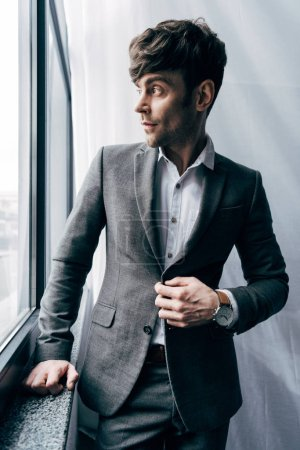 handsome businessman adjusting jacket and looking at window in office