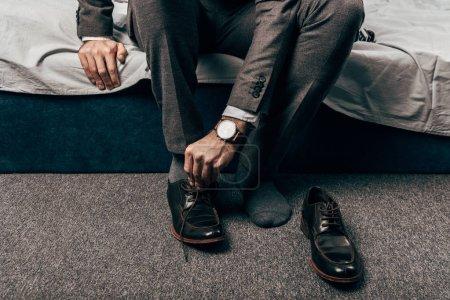 Photo pour Cropped image d'homme d'affaires mise sur les chaussures dans la chambre à la maison - image libre de droit