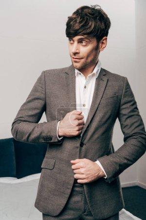 bel homme d'affaires gaie mettant sur veste