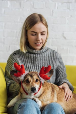 Photo pour Heureuse jeune femme assise sur le canapé et transportant chien corgi avec cornes de cerf de Noël - image libre de droit
