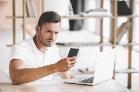 Photo pour Portrait d'homme d'affaires ciblé à l'aide de smartphone sur lieu de travail avec ordinateur portable au bureau - image libre de droit