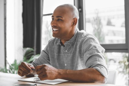 Photo for Portrait of cheerful african american businessman sitting at workplace in office - Royalty Free Image