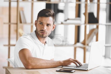 portrait of pensive businessman looking away while working on laptop at workplace in office