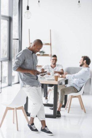 Foto de Hombre afroamericano usando tableta mientras colegas hablar de estrategia en el lugar de trabajo en oficina - Imagen libre de derechos