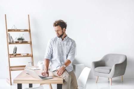 Photo for Focused businessman sitting on table and working on laptop in office - Royalty Free Image