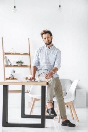 Foto de Hombre de negocios joven sentado en la mesa con el portátil en la oficina moderna - Imagen libre de derechos