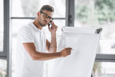 businessman talking on smartphone while making presentation at white board in office