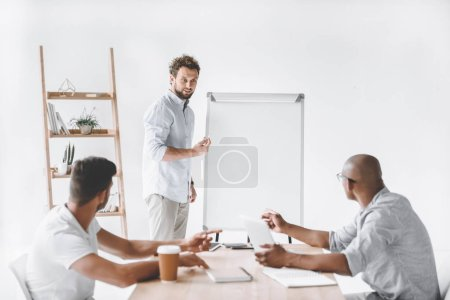 Photo for Young businessman at white board making presentation to colleagues - Royalty Free Image
