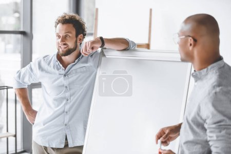 multiethnic businessmen standing near white board during business presentation