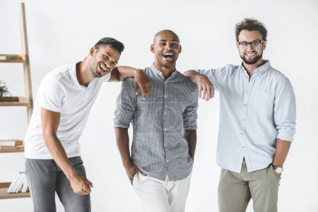 multiethnic group of young smiling businessmen standing in light office