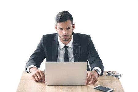 Photo pour Portrait d'homme d'affaires ciblée travaillant sur ordinateur portable sur le lieu de travail isolé sur blanc - image libre de droit