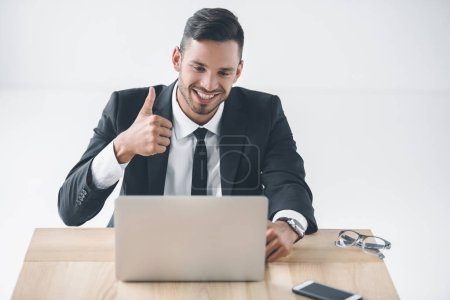portrait of smiling businessman showing thumb up at workplace with laptop isolated on white