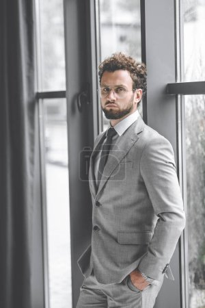Photo for Confident businessman in suit with hands in pockets looking at camera - Royalty Free Image