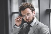 Portrait de confiance homme d'affaires élégant en lunettes et costume regardant la caméra