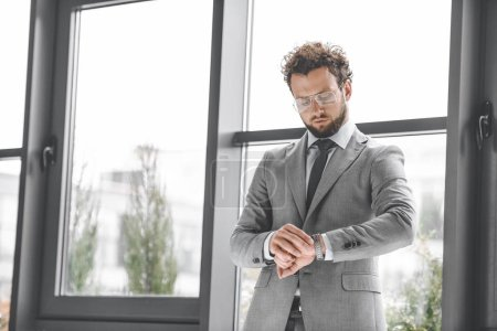 Photo for Portrait of handsome businessman in eyeglasses looking at watch to check time - Royalty Free Image