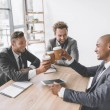 multicultural group of smiling businessmen clinking disposable cups of coffee at meeting