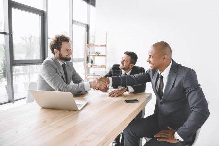 Foto de Multiétnicos empresarios sonrientes estrechándole la mano en reunión de trabajo con ordenador portátil - Imagen libre de derechos