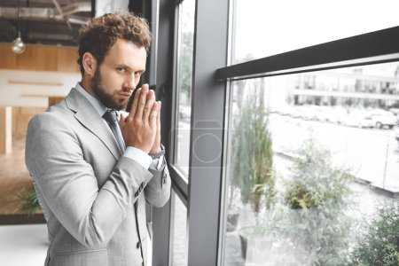 portrait of caucasian businessman standing at window in office and praying