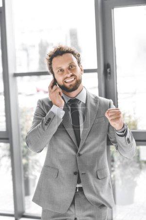 Photo pour Portrait de jeune homme d'affaires heureux parler sur smartphone au bureau - image libre de droit