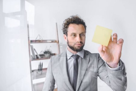 portrait of focused businessman point at sticky note in office