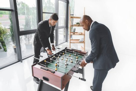 concentrated business people playing table football in office