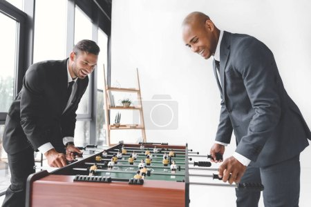 side view of happy businessmen playing table football together