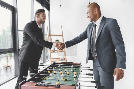 side view of smiling businessmen shaking hands after playing table football together