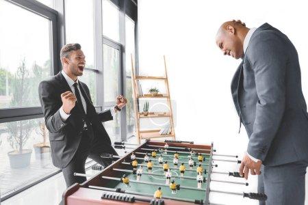 Photo pour Heureux homme d'affaires jouant au football de table avec une collègue au bureau - image libre de droit