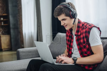 handsome teenager with headphones playing game on laptop