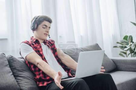Photo for Teen boy with headphones playing game on laptop while sitting on sofa - Royalty Free Image