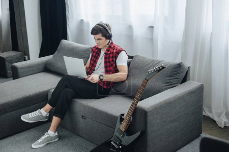 teenager with headphones playing game on laptop while sitting on sofa with electric guitar near
