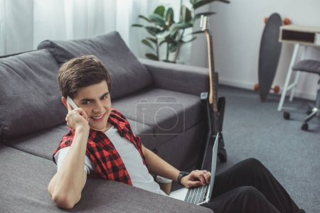 handsome smiling teenager talking on smartphone and using laptop