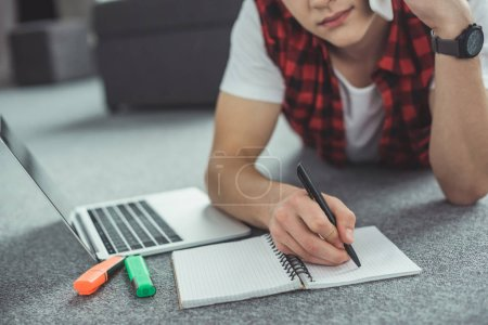cropped view of teenager talking on smartphone while doing homework and lying on floor