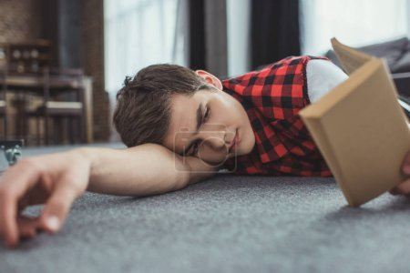 teenager studying and reading book while lying on floor