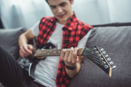 selective focus of teenager playing electric guitar at home