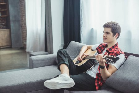 Photo for Happy teenager playing acoustic guitar on sofa at home - Royalty Free Image