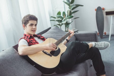youth teenager playing acoustic guitar on sofa