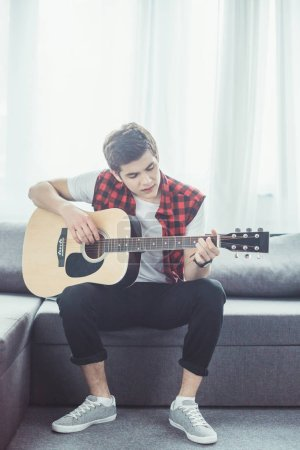young guitarist playing acoustic guitar at home