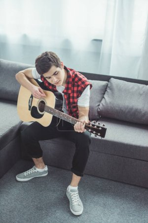male teenager playing acoustic guitar on sofa at home